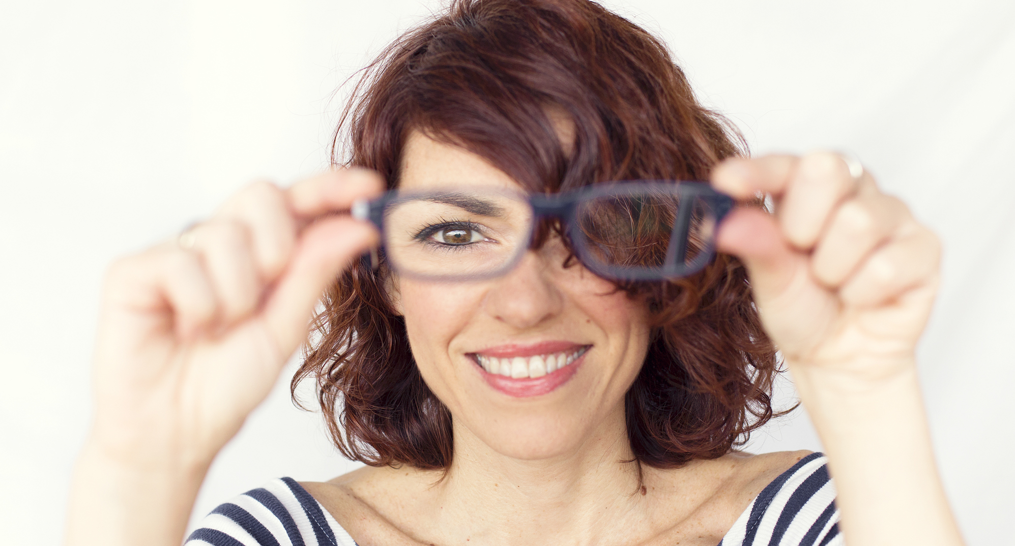 Woman holding glasses in front of her face