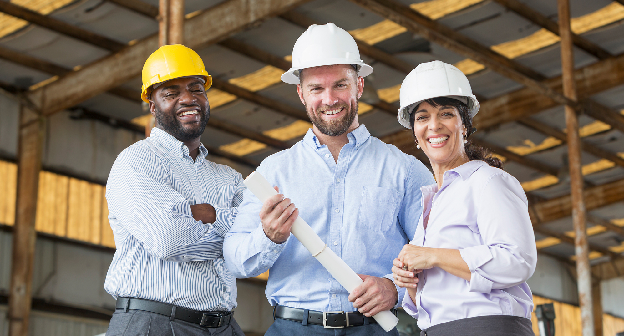 3 people standing in warehouse with hardhats