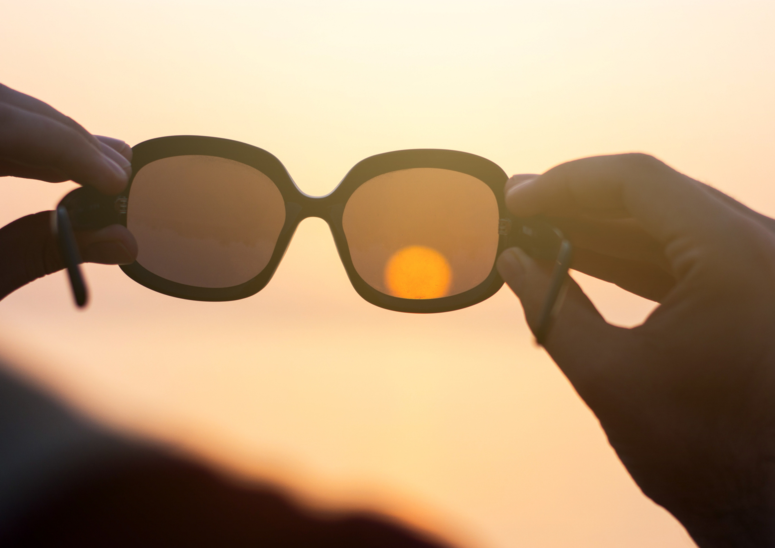Person holding sunglasses up to sun