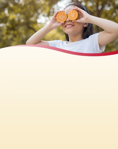 Girl holding orange halves in front of her face